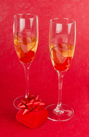 Two champagne goblets with jeweller box on red photo