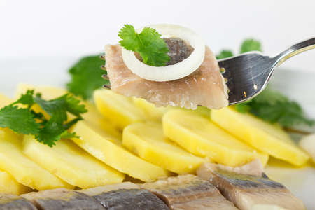 Portion of herring fish fillets with potato and onion photo