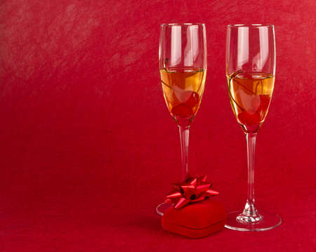 Two Valentine s champagne glasses with jewelery on white background Stock Photo - 17197545