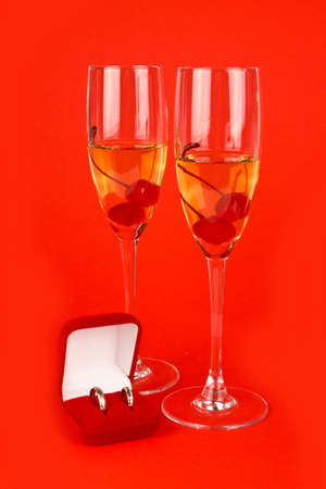 Two Valentine s champagne glasses with jewelery on white background photo