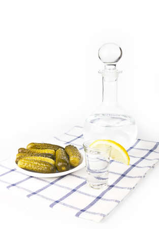 Russian traditional vodka with lemon and salty cucumber photo