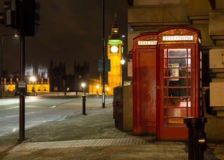 Traditional red phone booth in London with the Big Ben in the background at night photo
