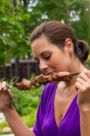 woman enjoying barbecue outdoors Stock Photo