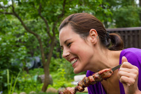 woman enjoying barbecue outdoors photo
