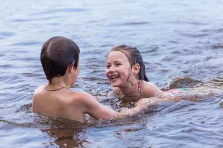 Little boy teaches his little sister to swim in a lake photo