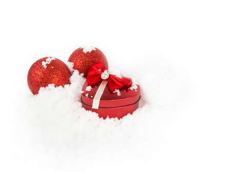 Red Christmas balls and heart on white