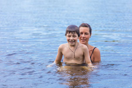 Mother and son swimming in the lake photo