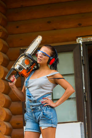 Pretty young woman builder with petrole-powered chain saw photo