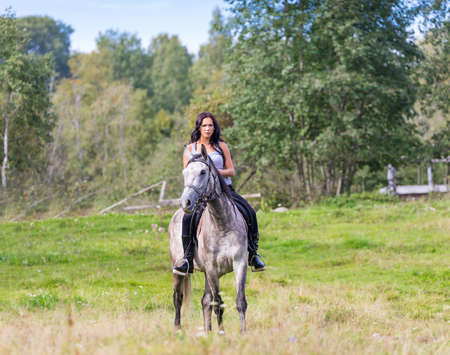 Elegant attractive woman riding a horse photo