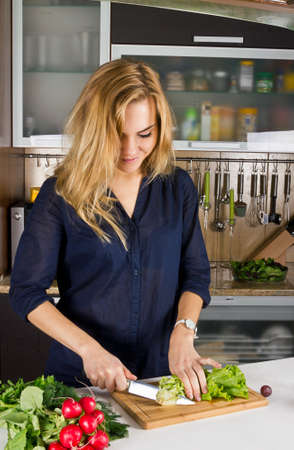 Young pretty young woman cooking salad in kitchen Stock Photo