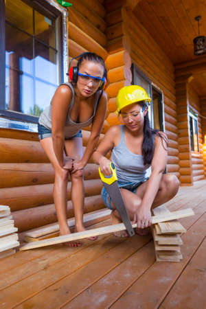 Pretty young woman builder with saw photo