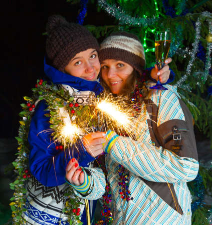 Two girls with Christmas champagne outdoors photo