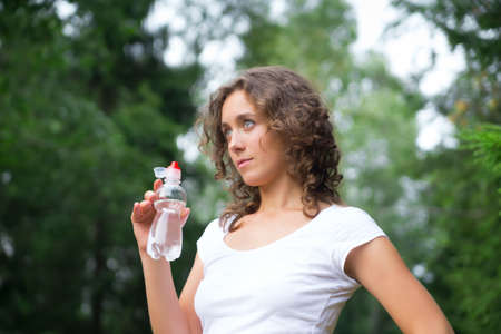 Pretty young woman drinks water photo