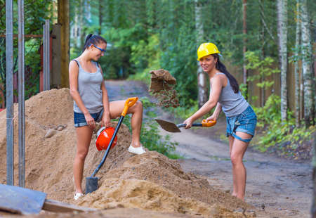 Pretty young woman builder digging a shovel photo