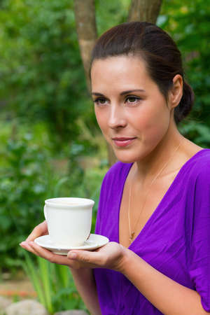 Beautiful young woman drinking coffee outdoors photo