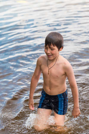 Little boy swimming in a lake photo