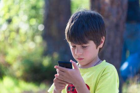 아이 야외에서 휴대 전화를 재생