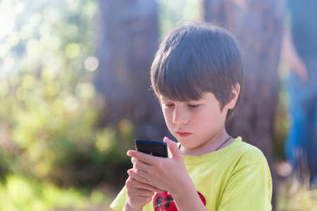 Child playing phone outdoors sunlight photo
