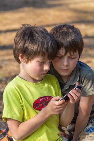 야외에서 휴대 전화를 노는 아이 소년
