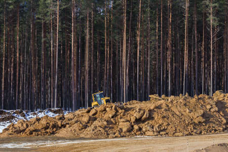 Yellow excavator at work in winter forest photo