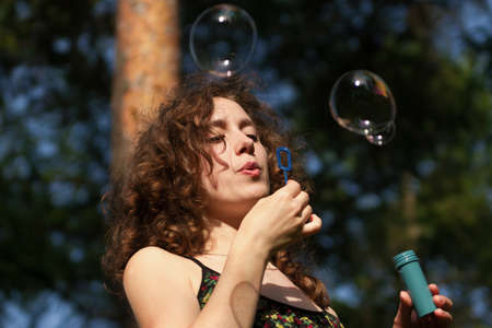 Young pretty woman blowing soap bubbles in park photo