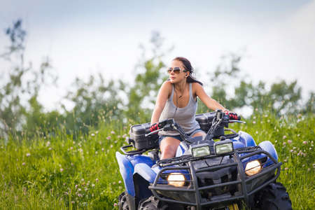 Elegant woman riding extreme quadrocycle in summer fields Stock Photo