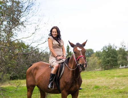 Elegant attractive woman riding a horse farm photo