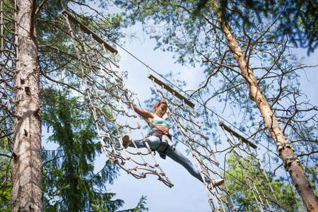 13 July 2014, Russia, Saint-Petersburg, adventure park \Norwegian wood\. Young brave woman climbing in a adventure rope park photo