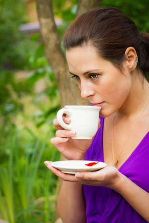 Beautiful young woman drinking hot coffee outdoors photo