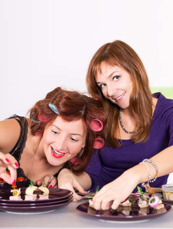 Two young pretty woman housewife cooking with curlers on hair photo