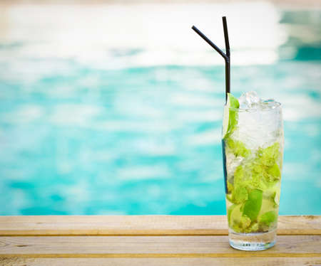 pool bars: Mohito mojito drink with ice mint and lime near swimming pool Stock Photo