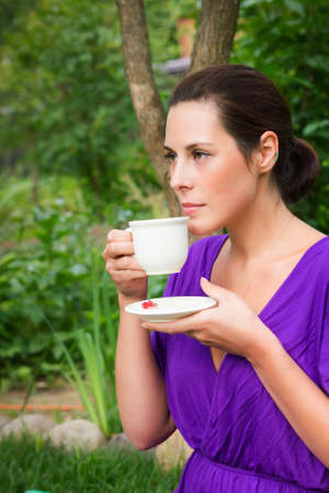 brunete: Beautiful young woman drinking coffee outdoors Stock Photo