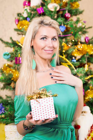 Pretty woman with present near Christmas tree photo