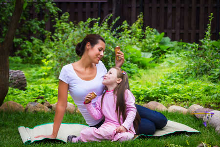 Mother and daughter eat ice-cream on grass outdoors photo