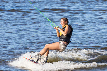Woman study riding on a wakeboard outdoors