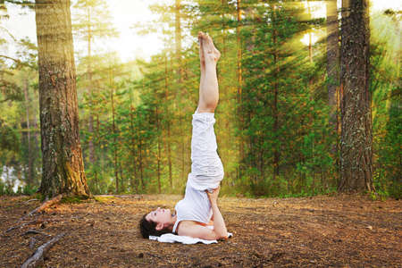 Yoga shoulder stand in the autumn forest