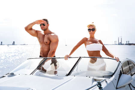 Elegant beautiful couple on a boat in a swim wear