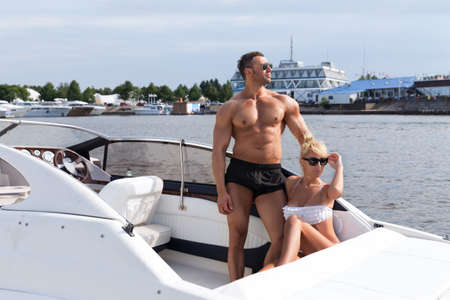 Elegant beautiful couple on a boat in a swim wear Stock Photo - 41395300