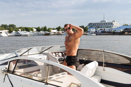 sexy abs: Muscle man on a boat Stock Photo