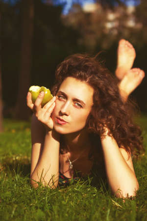 outdoor eating: beautiful young woman eating apple outdoors in spring