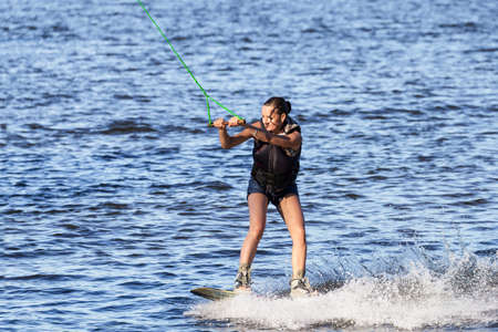 wakeboarding: Young woman study riding wakeboarding on a lake