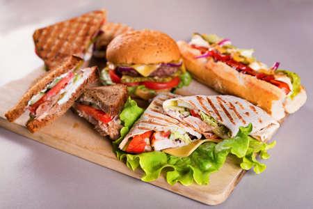 sandwich de pollo: placa de comida r�pida con s�ndwiches de hamburguesas y hot dog envoltura de pollo Foto de archivo