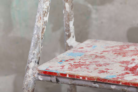 stucco: Old painted and stucco ladder on concrete wall background