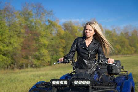 atv: Elegant woman riding extreme quadrocycle ATV outdoors Stock Photo