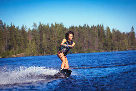 wakeboarding: Woman study wakeboarding on a lake outdoors Stock Photo