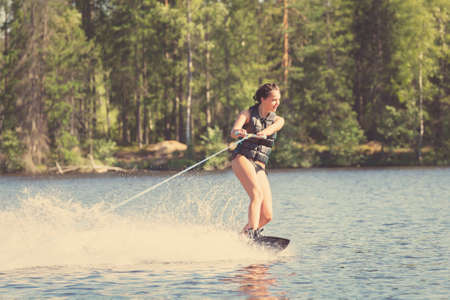 Young pretty woman study riding wakeboard on a lake