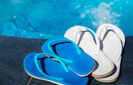 swim shoes: Blue slippers near swimming pool - holiday concept
