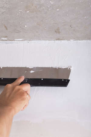 stucco house: house improvement by worker puts finishing layer of stucco on the wall using a plastering trowel
