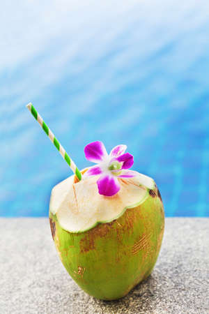 fruit water: Fresh coconut drink with orchid flower near swimming pool