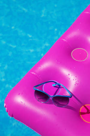 lilo: Sunglasses on a pink air mattress in swimming pool. Tropical summer concept.